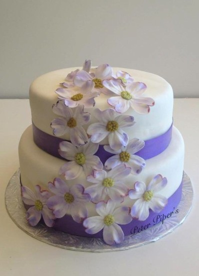 Elegant wedding cake with cascading white flowers that have been lightly airbrushed.