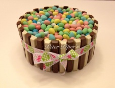 Chocolate sponge filled with a mini egg cream wrapped in white and milk chocolate kitkat chocolate bars and topped with mini eggs