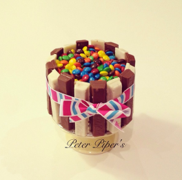 Chocolate sponge with vanilla buttercream wrapped in white & milk chocolate kitkats and topped with mini m&m's
